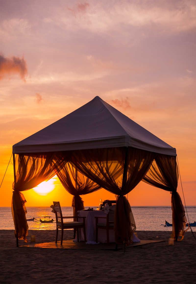 日落时海滩上用于晚餐的棚