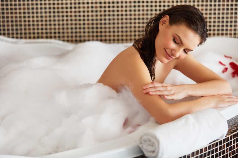 在充满白色泡沫的浴缸里洗澡的美女