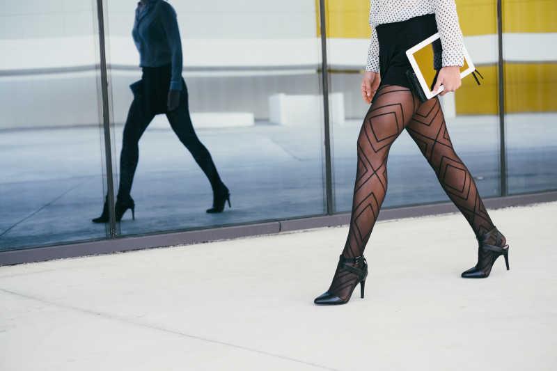白色背景下穿着黑色职业短裙的美女腿部