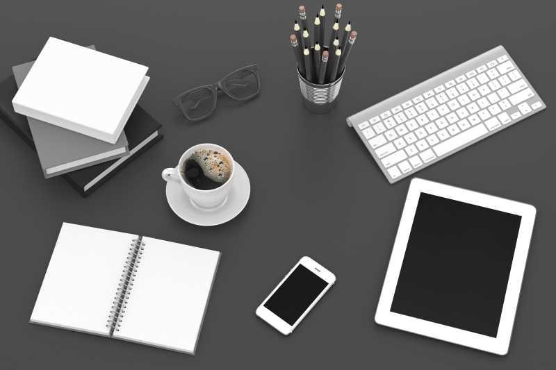 灰色桌面上的平板电脑智能手机笔记本和咖啡杯等