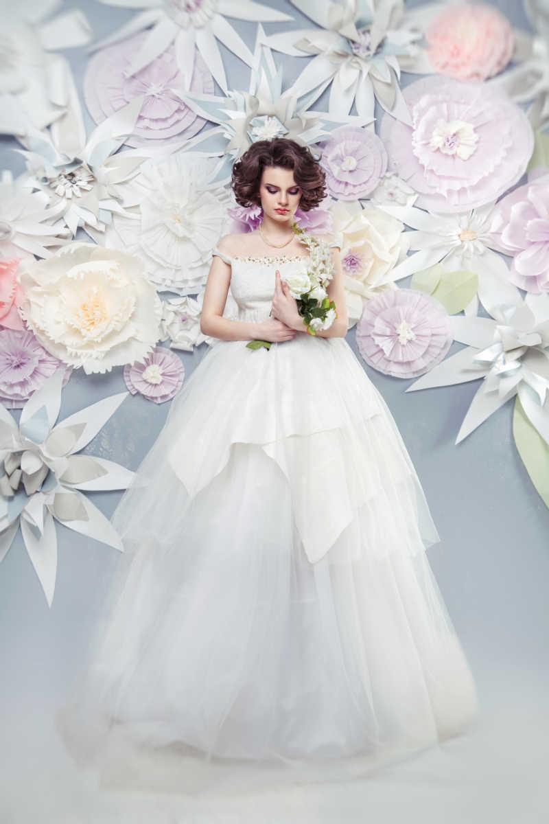纸花背景前穿着婚纱的新娘