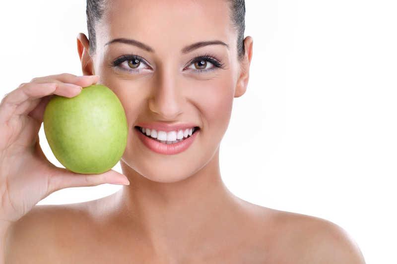白色背景下拿着绿苹果微笑露出牙齿的美女