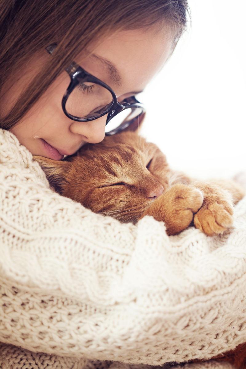 可爱的小女孩抱着睡着的猫咪