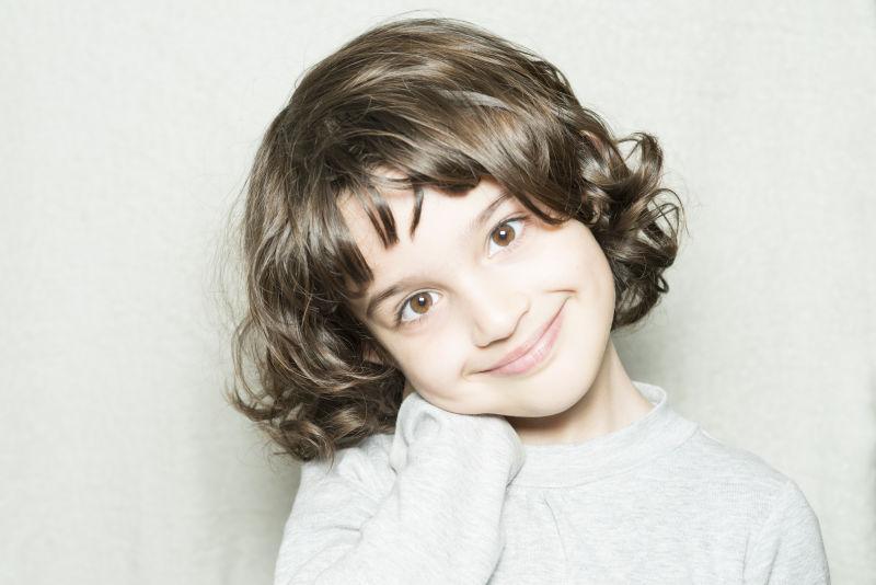 可爱的卷发小女孩对着镜头微笑