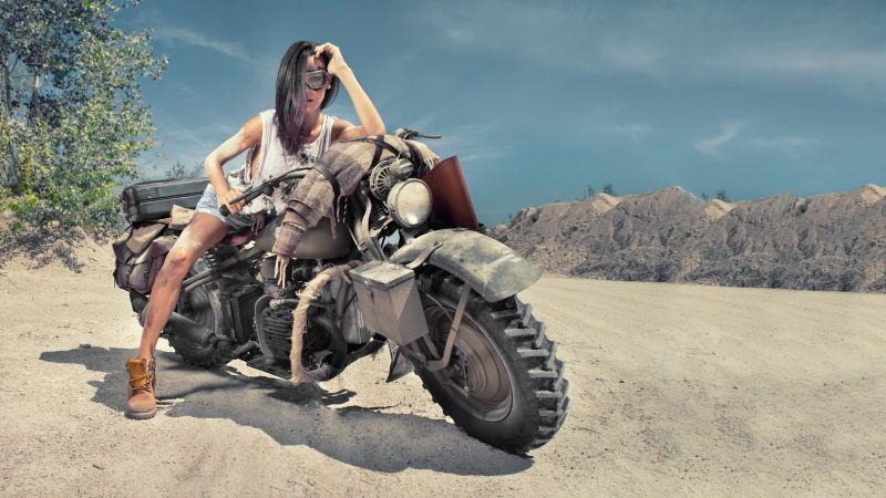 摩托车旁拿枪的酷拽女人与健身美女的教练图片