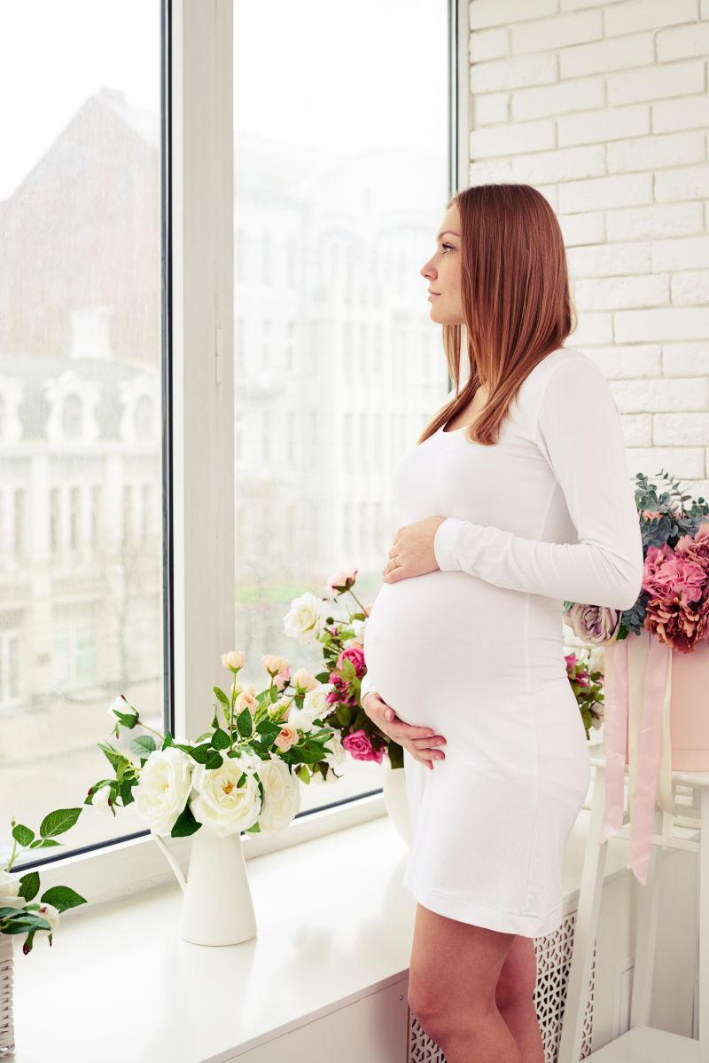 用手托着肚子站在孕妇视频的白色包超手墙边图片