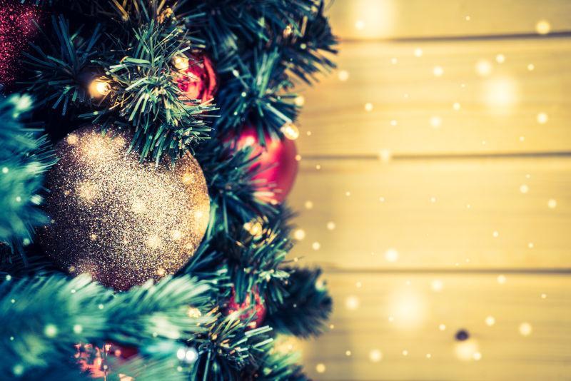 黄色木板上的圣诞树枝和各种圣诞饰品