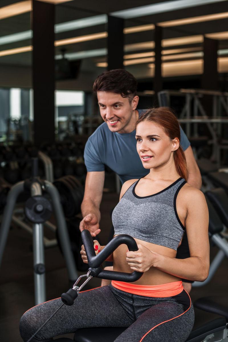 健身房私人美女教练_一个年轻的女士在健身教练指导下健身图片-健身房里带着私人男 ...