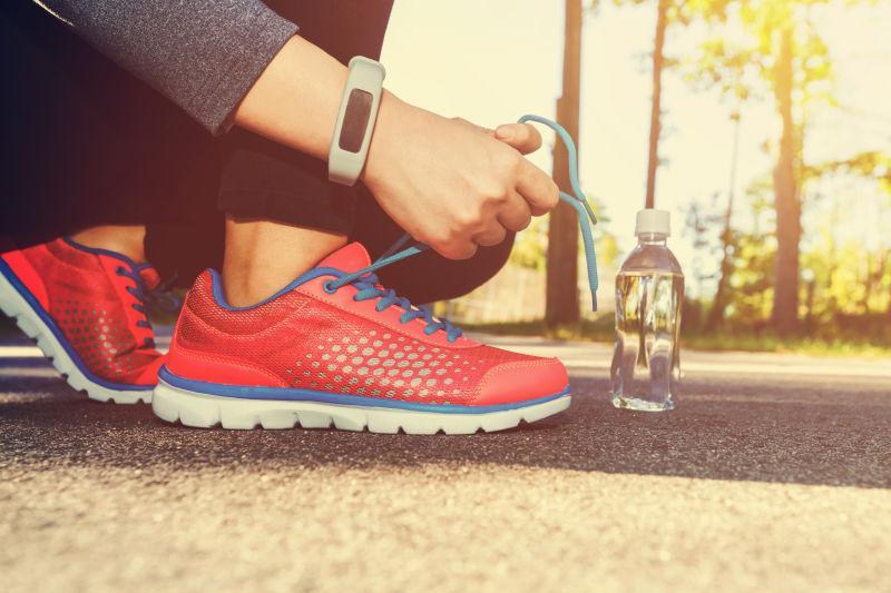 在水瓶旁边系鞋带的女性跑步者