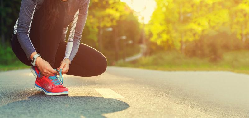 在路边系着鞋带的女性跑步者