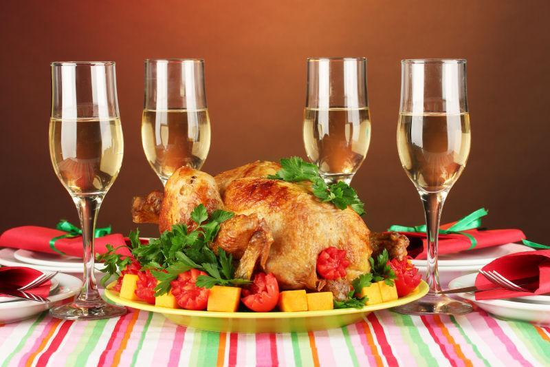 棕色餐桌上的烤鸡与美酒