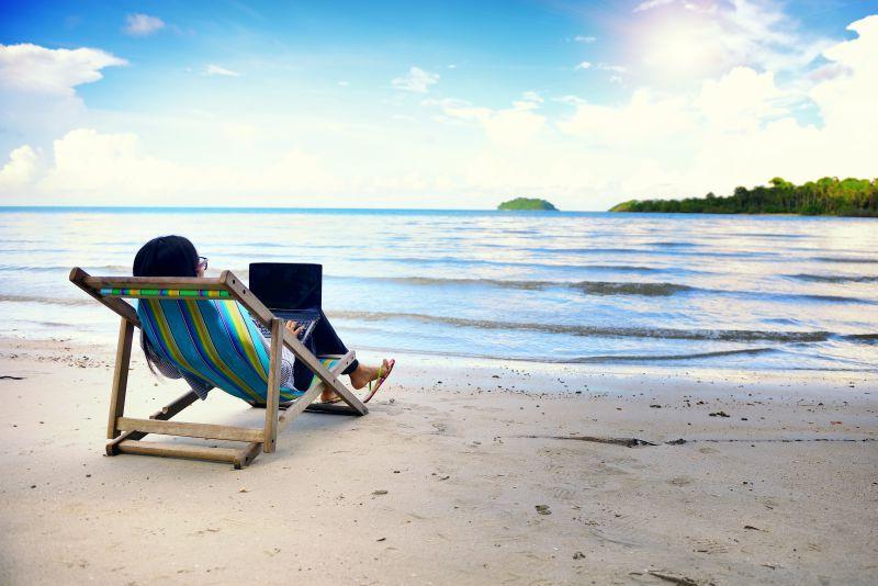 海边沙滩旁躺在躺椅上使用笔记本电脑的女人