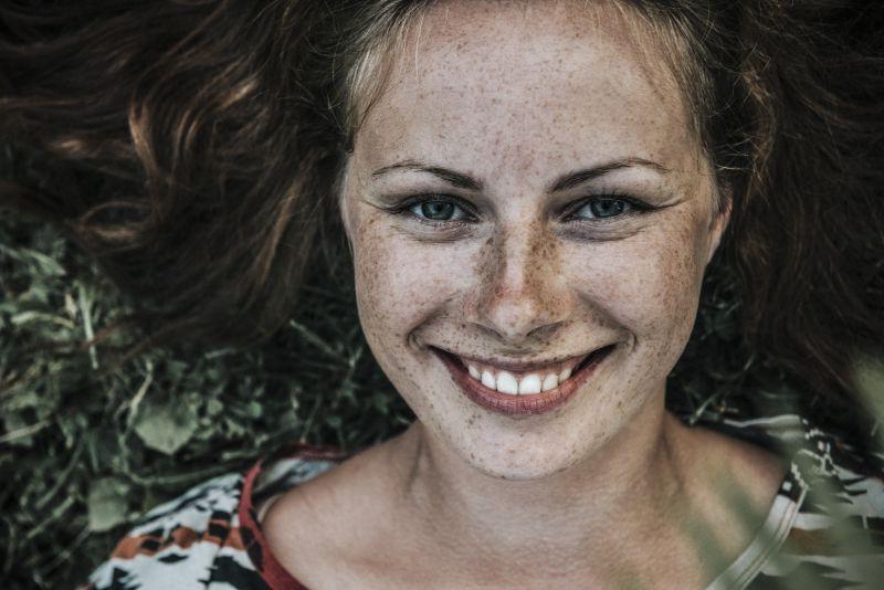 黑色背景上脸上有雀斑的微笑着的美女