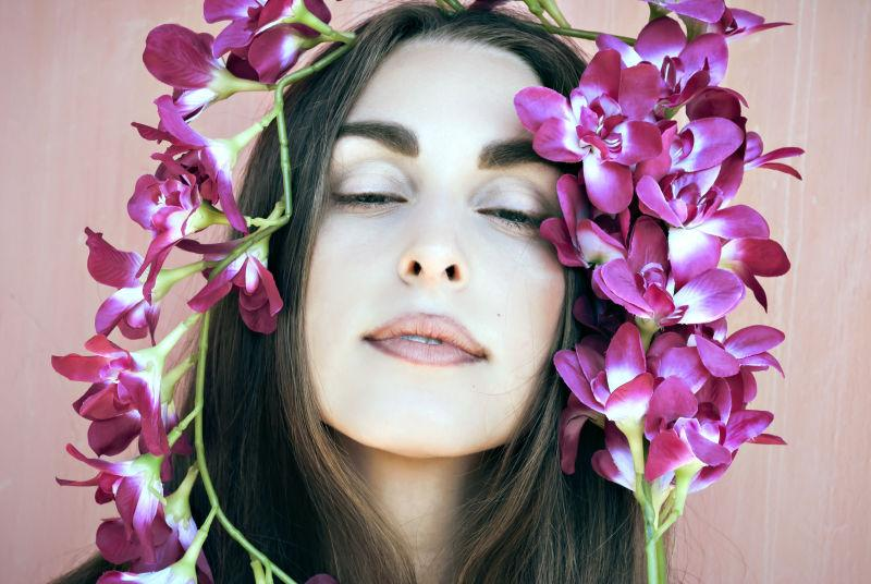 被紫色兰花包围的漂亮女孩