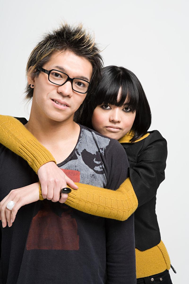 灰色背景下的亚裔90年代年轻情侣