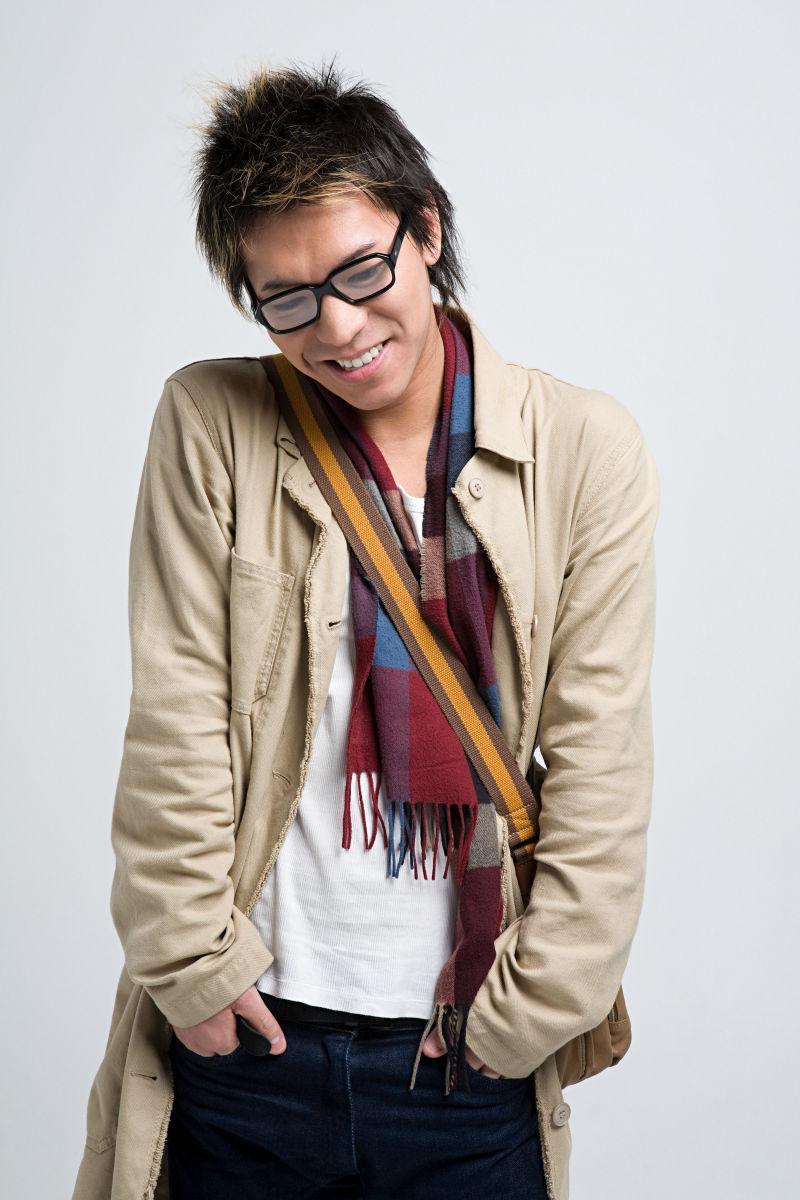 白色背景下戴着眼镜手抄兜的亚裔男子