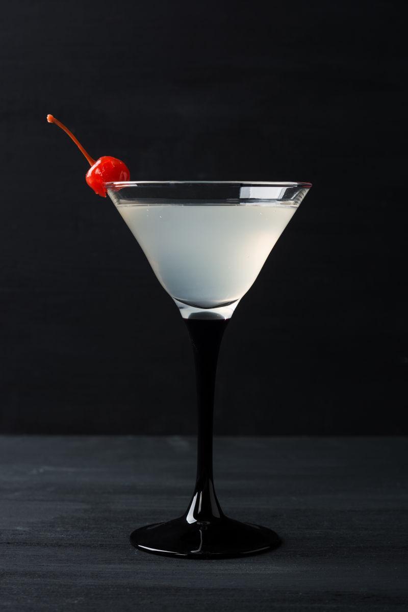 黑色背景上的带有樱桃装饰的马蒂尼酒杯鸡尾酒