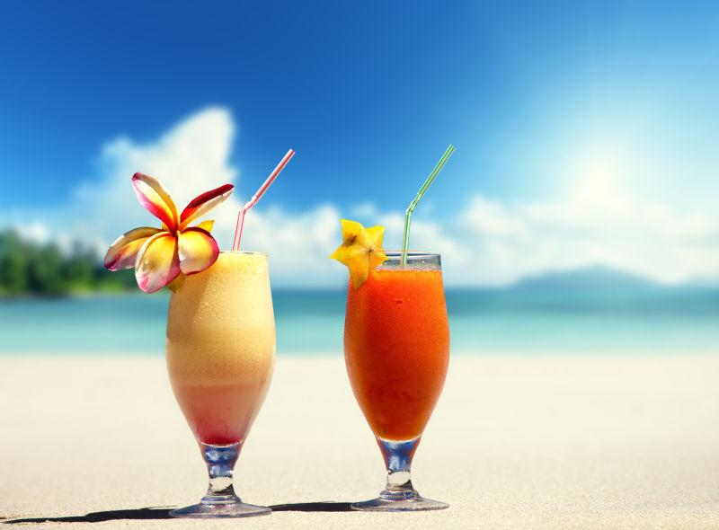 沙滩背景上两杯鸡尾酒