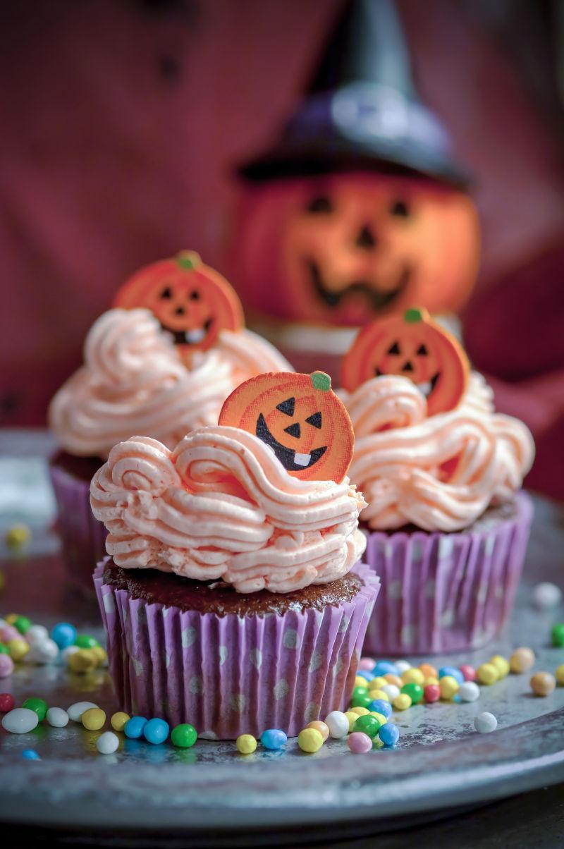 散落着彩色糖果的桌上的万圣节纸杯蛋糕