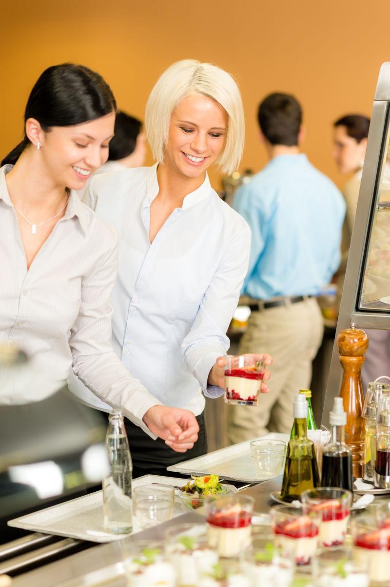 自助餐厅年轻女子看甜点选择服务托盘