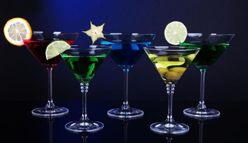 深蓝色背景下马蒂尼酒杯中的酒精鸡尾酒