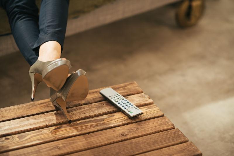 把腿翘在木桌上的高跟鞋女人