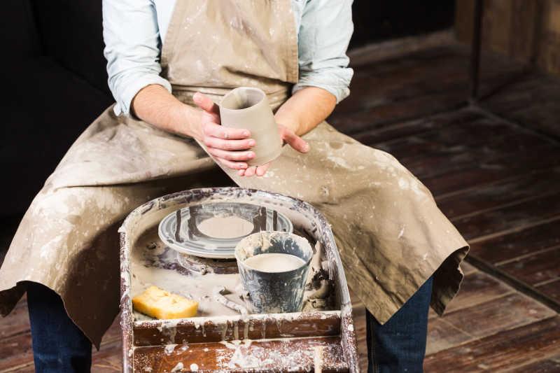 工匠双手不烧粘土杯对的产品在进一步加工