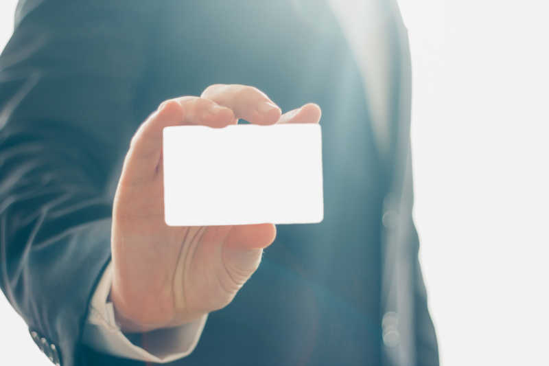 名片持有人在白色和明亮的背景下手拿名片