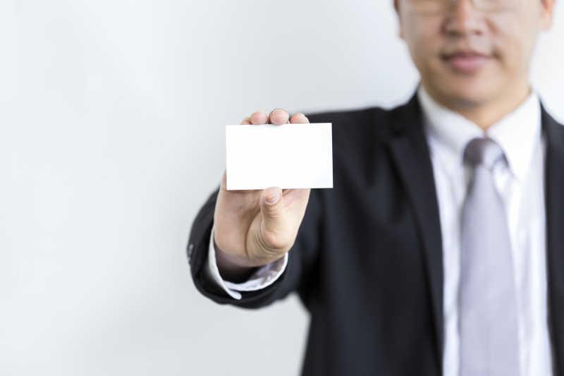 一个戴眼镜微笑的男人手拿白色名片
