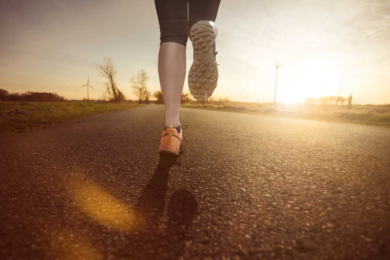 妇女跑步在日落