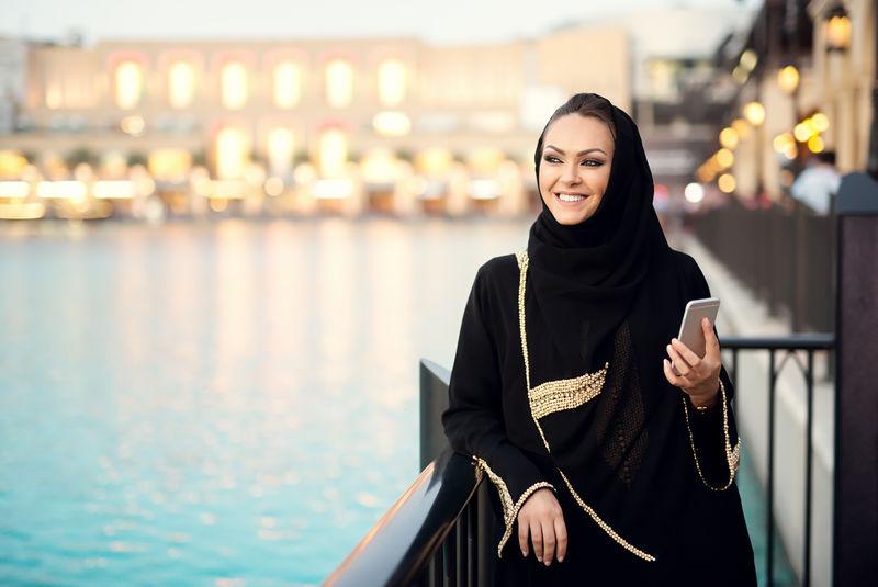 阿拉伯女人用智能手机打字,微笑着,一边看一边。