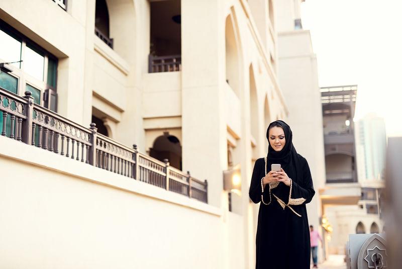 穆斯林妇女走路和打字信息。