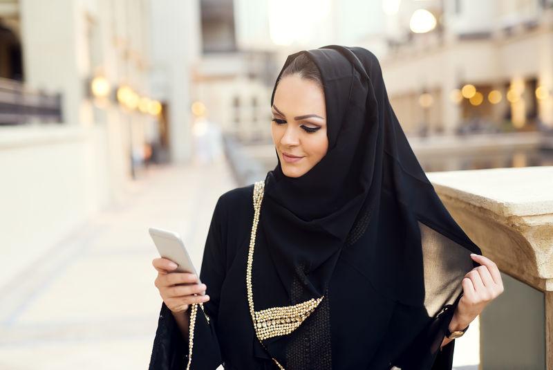 阿拉伯妇女用智能手机打字,微笑着。
