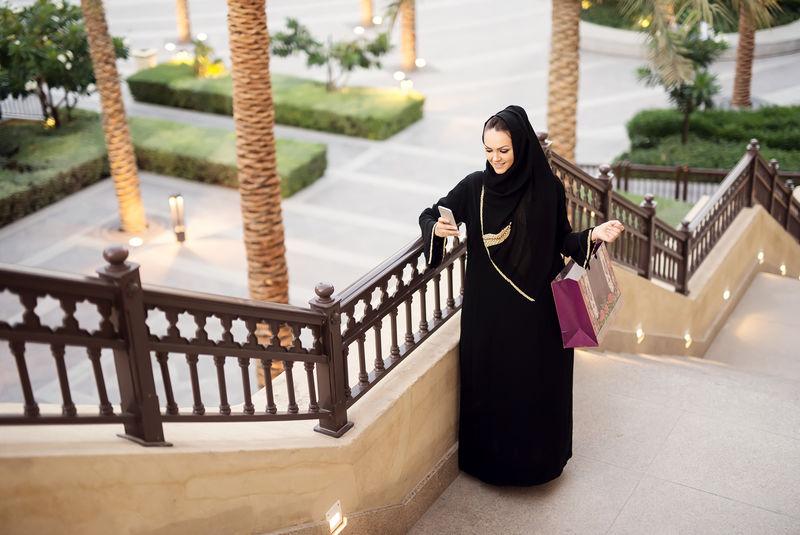 穆斯林妇女拿着购物袋和智能手机。键入消息。