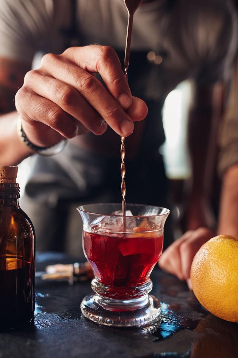 调酒师用手搅动一杯意大利式鸡尾酒
