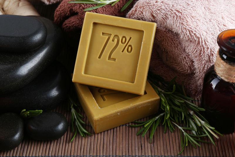 用迷迭香枝条手工制作的香皂-用迷迭香油和毛巾装瓶-特写镜头-迷迭香水疗概念