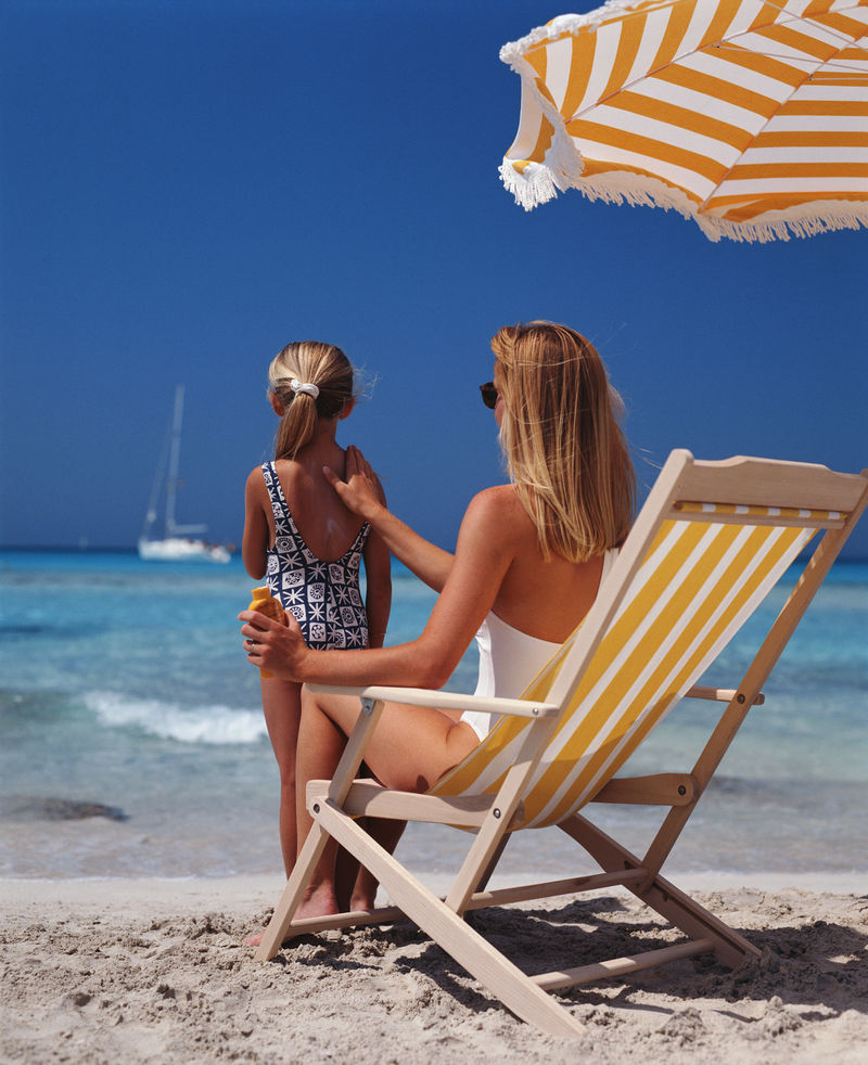 坐在沙滩椅上-穿着泳装-微笑着的现代母亲和女儿远眺远方