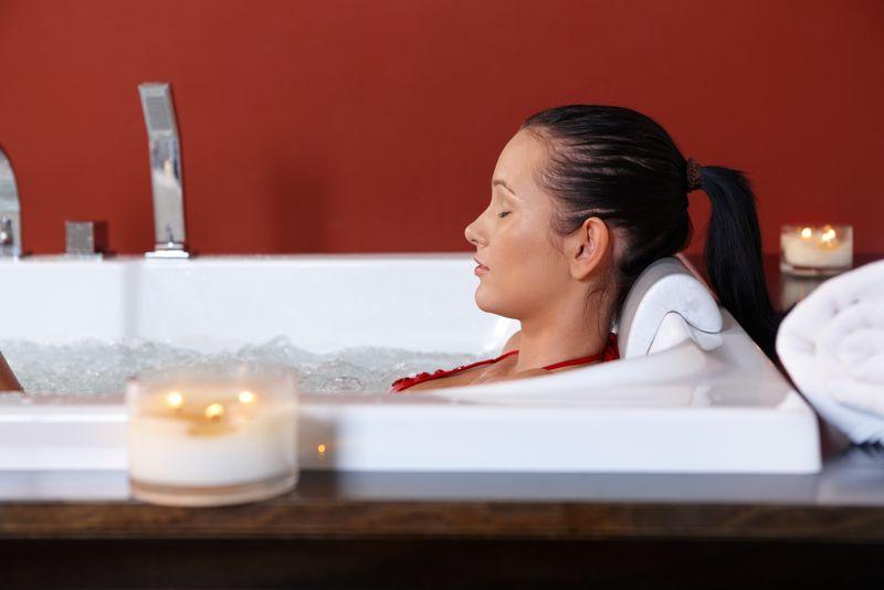 年轻女子在烛光下闭上眼睛享受健康泡泡浴