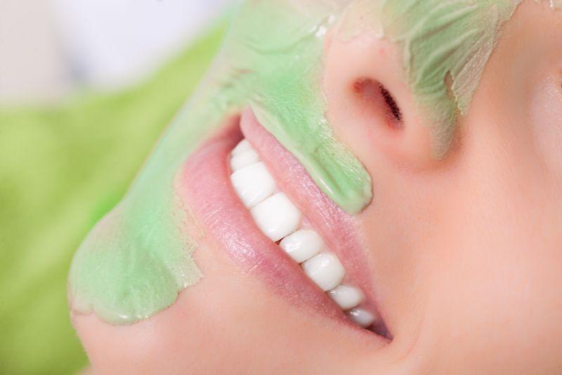 美容治疗理念-在水疗沙龙放松的女人-化妆师在女性脸上涂粘土面膜-身体护理健康的生活方式