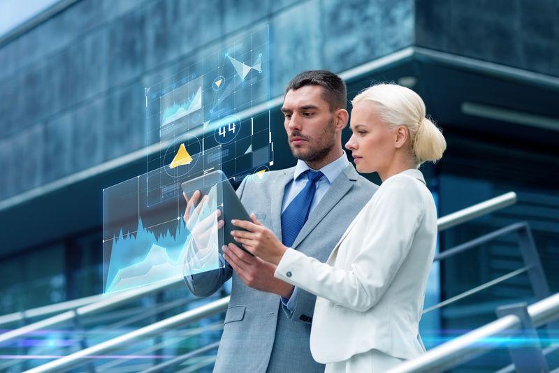 商业、合作、技术和人的概念-商人和女商人在城市街道的虚拟屏幕上使用平板电脑电脑图表
