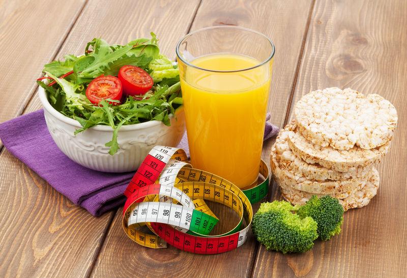 健康食品和木桌上的卷尺-健康与健康
