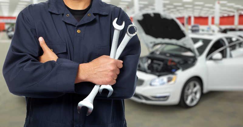 在汽车维修车间拿着扳手的修理工