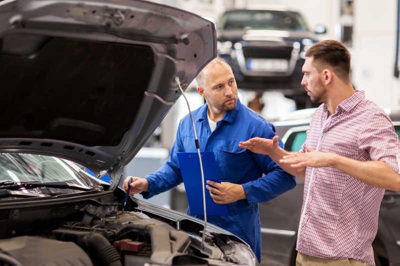 汽车维修车间的汽车修理工在汽车旁边商讨维修方案