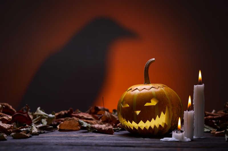 恐怖背景下的南瓜灯蜡烛和乌鸦