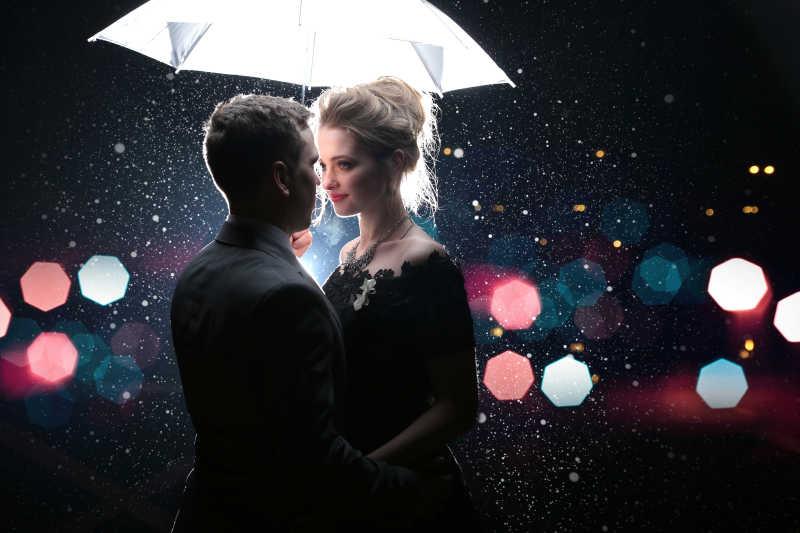 白色雨伞下的一对新婚夫妻