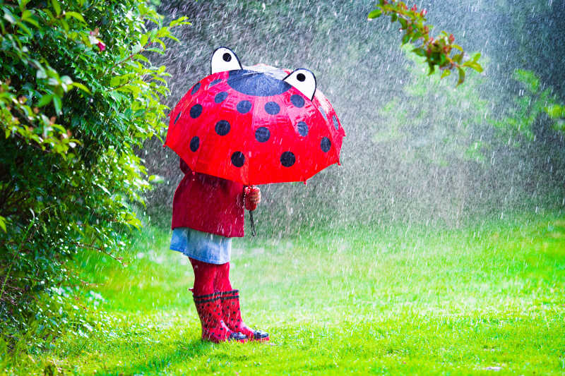 小孩子下雨天撑着伞在公园