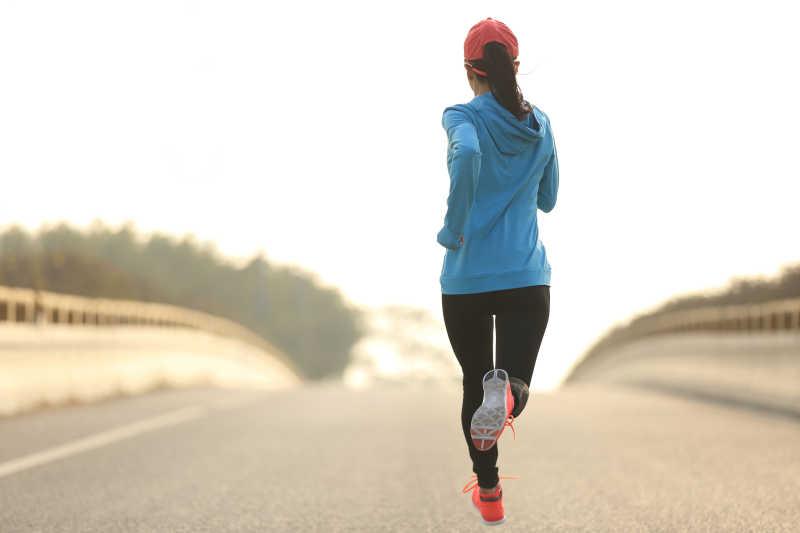 跑在路上的年轻女子健身运动员