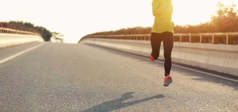 跑在路上的年轻女子跑步者