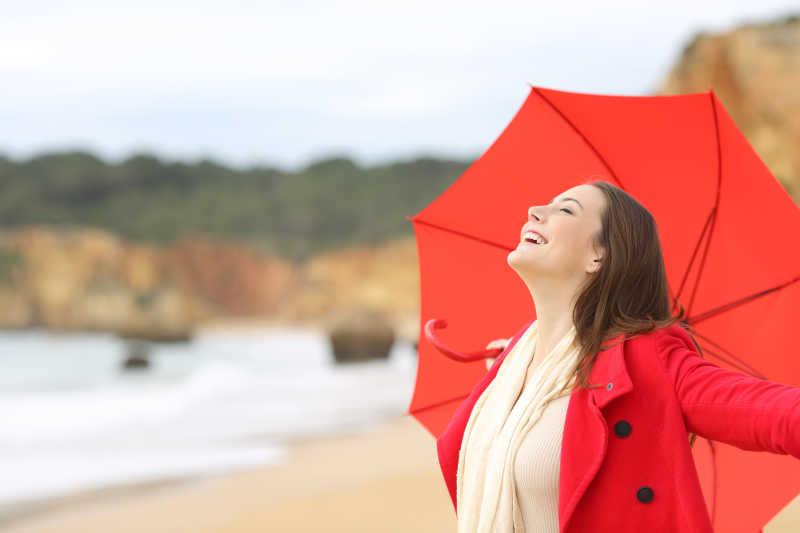 在海滩撑着红色雨伞的美女