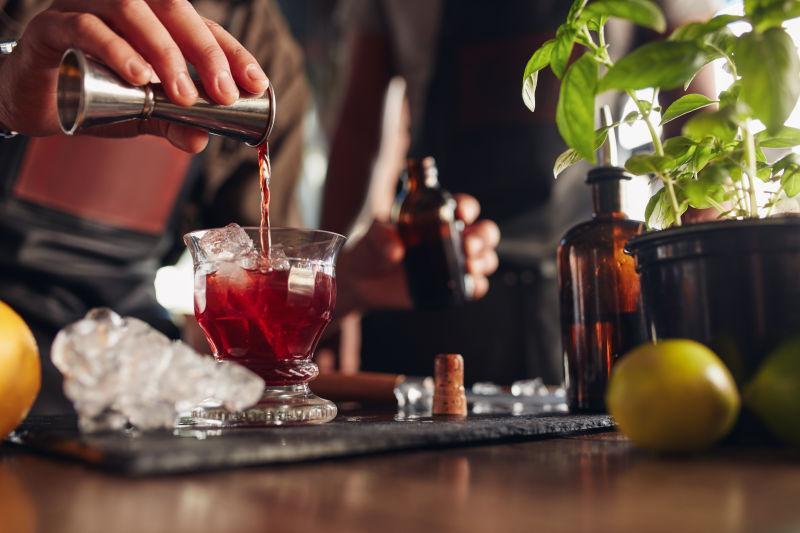 一个酒吧服务员把饮料从量杯里倒进鸡尾酒杯